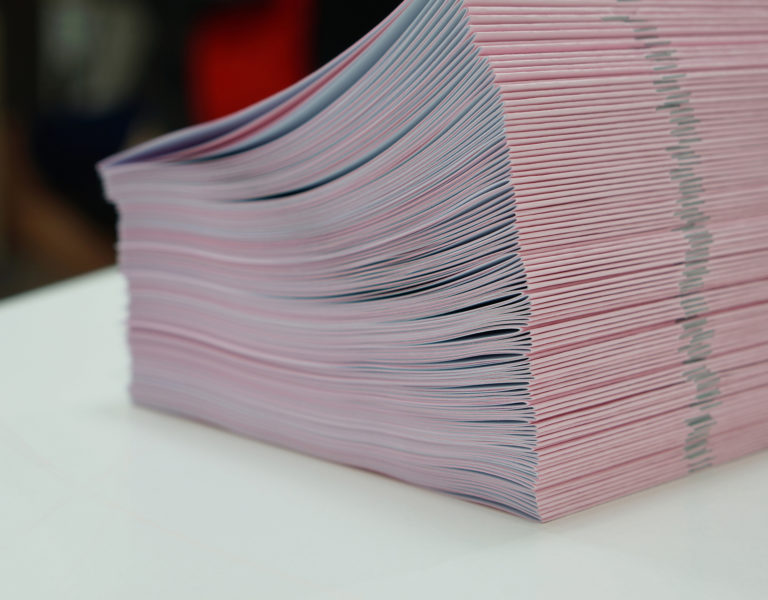 Piles of pink handout papers placed on table at office.